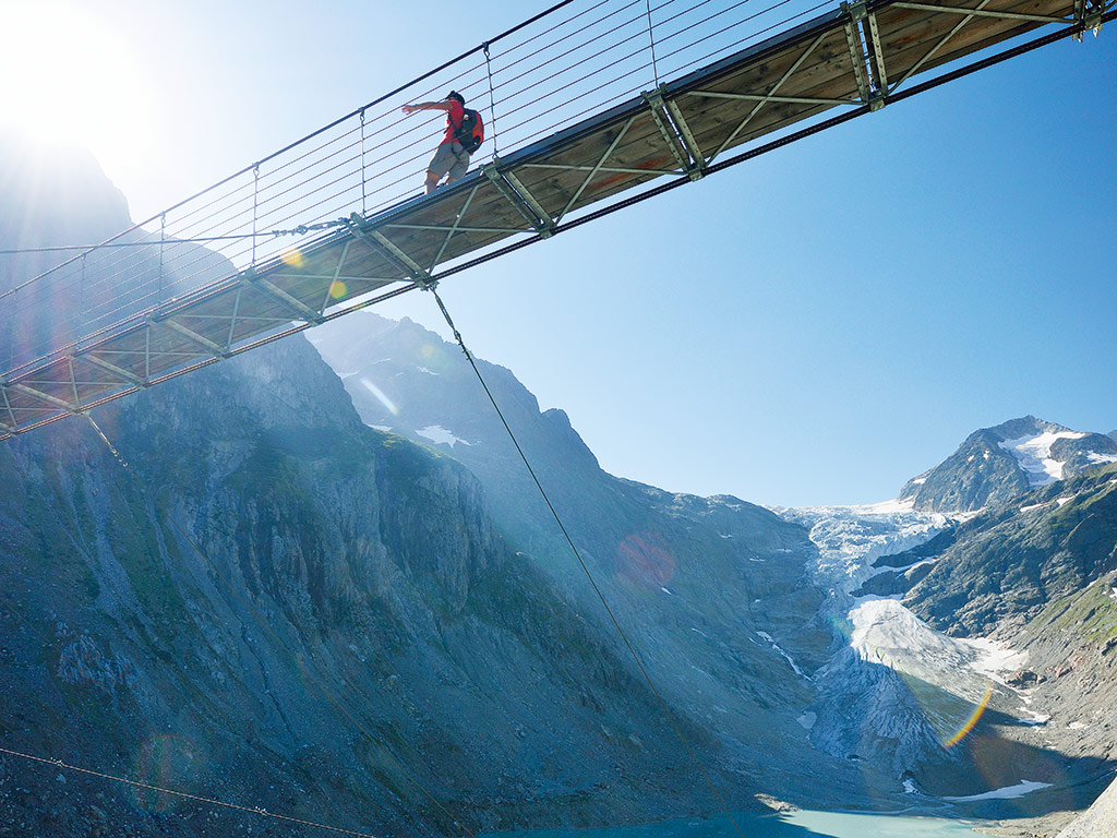 Man crossing a bridge in Switzerland