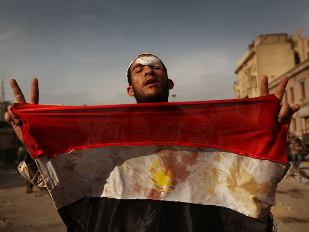 An anti-government protestor holds a blooded Egyptian flag in Tahrir Square in Cairo