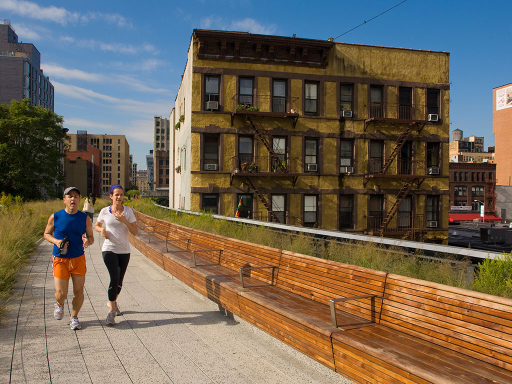 A couple jogs along High Line Park, making the most of inner-city public space away from busy roads