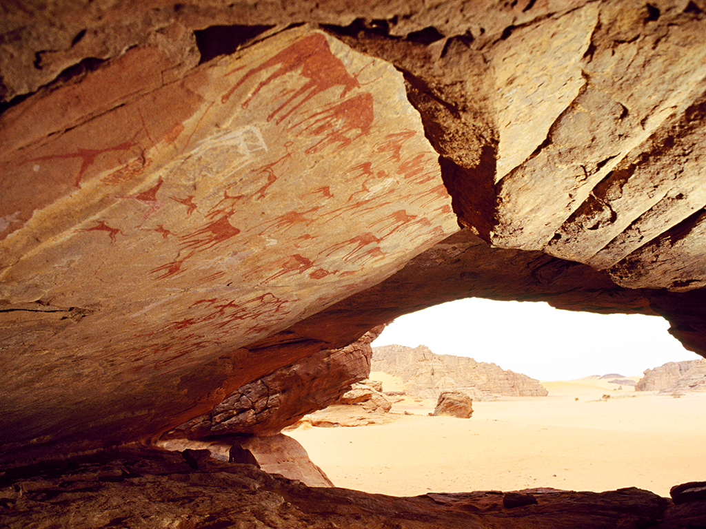 Looking out of a low cave in southern Algeria over a riverbed whose waters may not have flowed for several thousand years. Its roof is decorated with pastoral paintings made when the Sahara was green