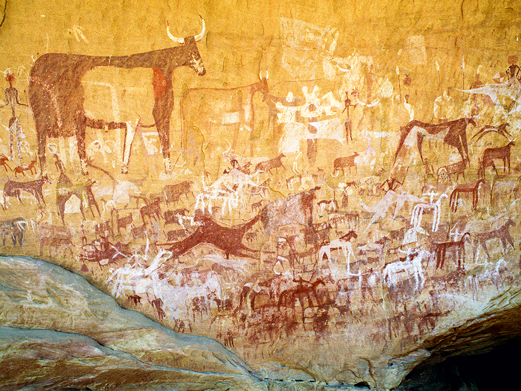 Richly decorated panel of paintings in northern Chad from the pastoral period of Saharan rock art. Images include decorated cattle, mounted camels, horses and warriors