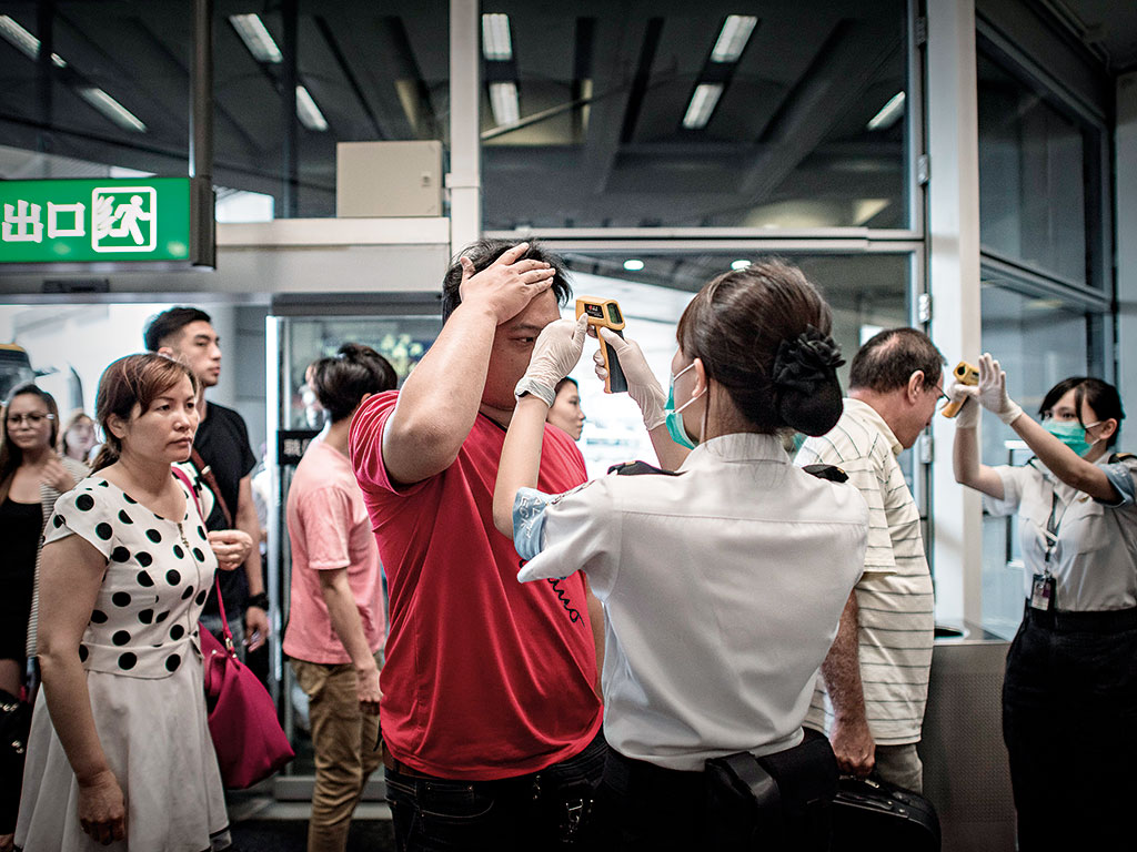 Passengers have their temperature checked by airport staff as part of preventive measures taken against the spread of MERS