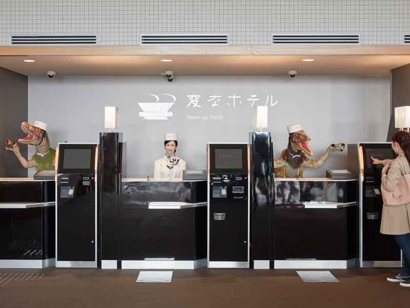 A guest is greeted at the front desk of Henn-na Hotel by a Japanese-speaking humanoid and an English-speaking Velociraptor robot