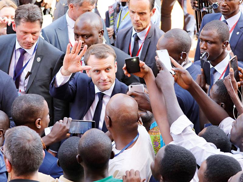 Emmanuel Macron leaving the University of Ouagadougou